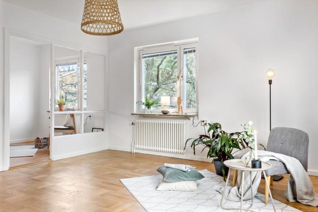 Vardagsrum med tidstypisk originalglasvägg in mot köket