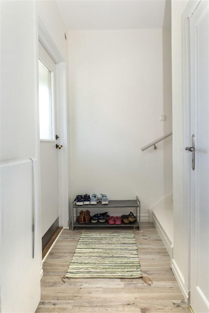 Välkomna in! Yttre hall med trapp till övervåningen och trapp ner till källarvåningen