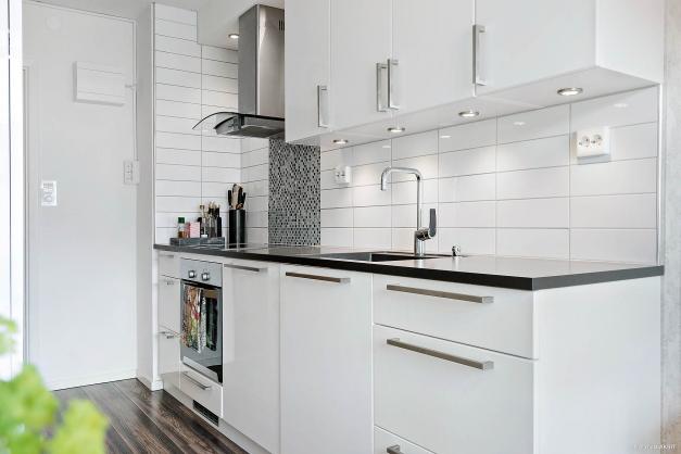Snyggt kök i vitt med mörk bänkskiva.