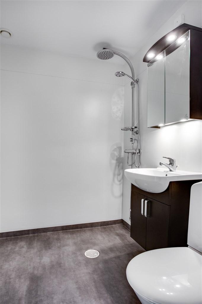 Helrenoverad dusch/wc i ljusa toner.