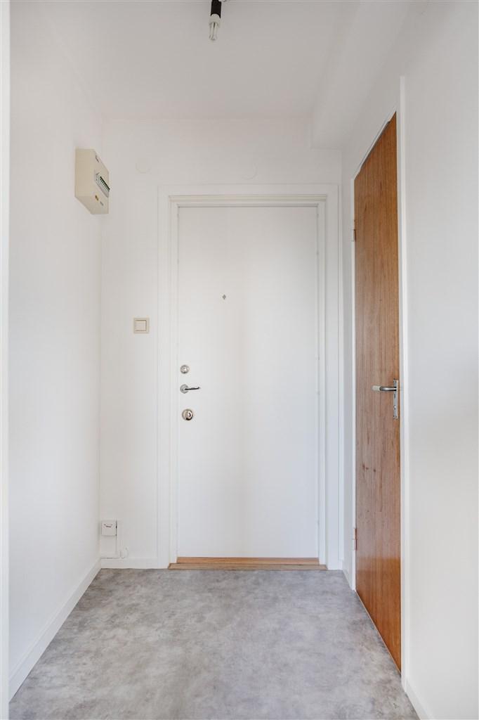 Ljus entréhall med ingång till dusch/wc.