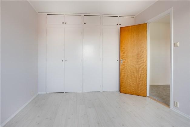 I sovrummet finns en hel garderobsvägg.