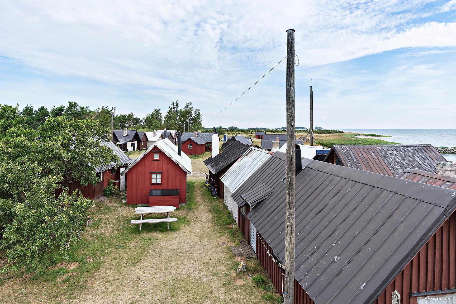 Fiskeläget söderifrån med boden längst till vänster till salu.