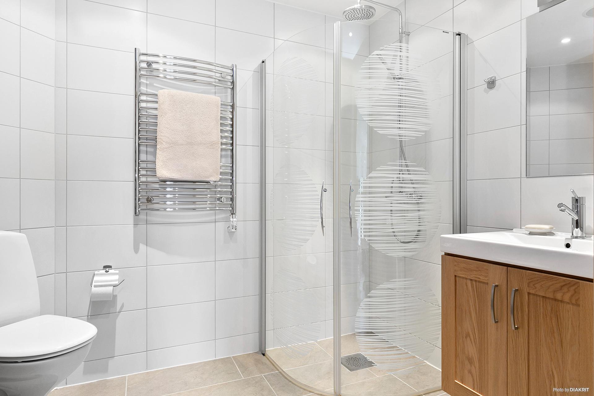 Badrum med dusch, handdukstork, wc, spegelskåp och tvättställ med komod.