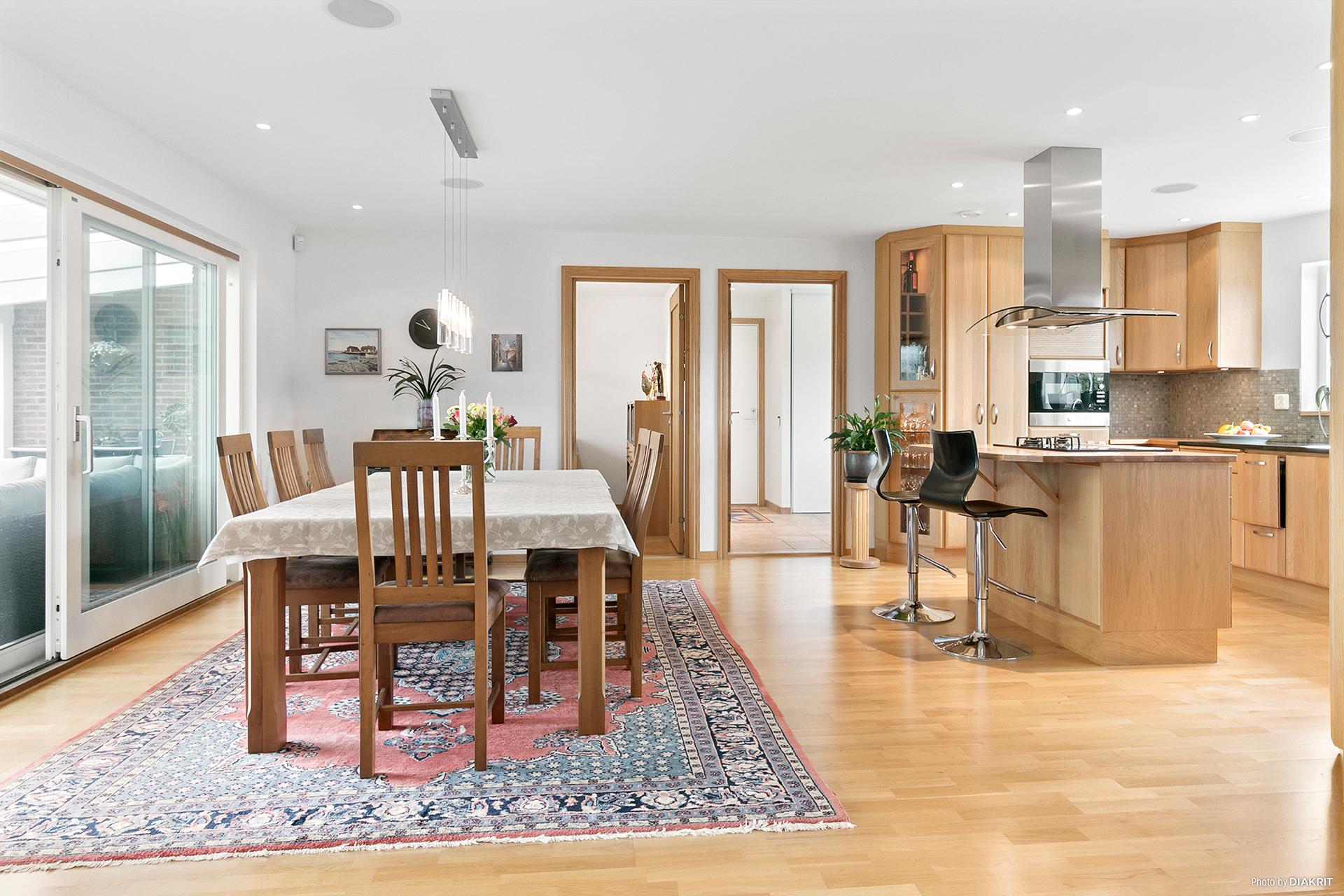 Öppet kök med köksö och utrymme för matbord.