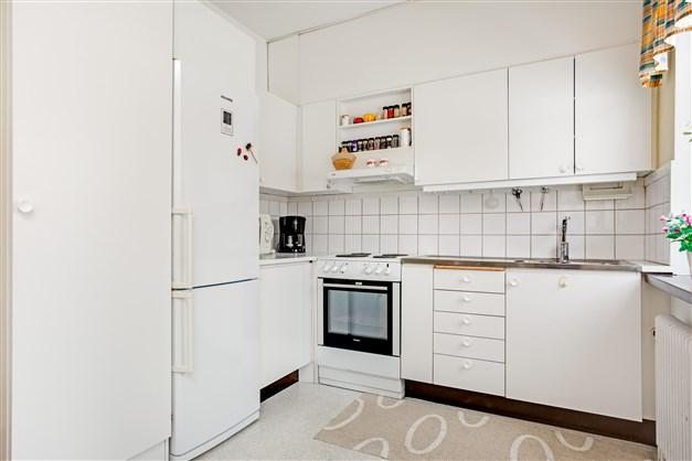 Köket har vit inredning och rostfri diskbänk. Här finns nyare kyl/frys och spis samt fläkt.