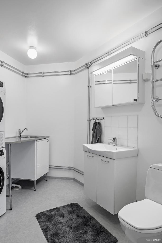 Rymligt badrum med wc, handfat med kommod samt tvättbänk med ho.