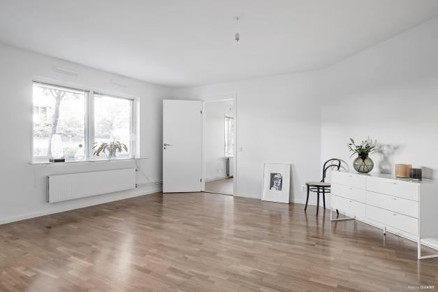 På golvet ligger parkett och dem stora fönstren ger ett ljuvligt ljusinsläpp.