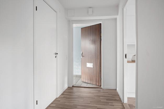 Välkomnande hall med samma laminatgolv som i kök och sovrummen för den enhetliga känslans skull.