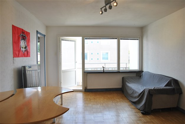 Vardagsrum med parkettgolv och utgång till balkongen