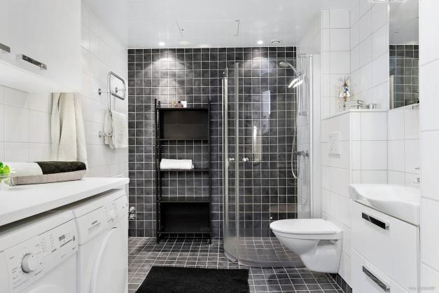 Ljust badrum i sobra färger med all utrustning som förväntas av ett modernt badrum.
