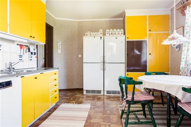 Äldre kök med gul inredning.