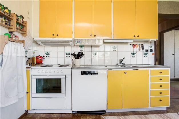 Köket är fullt utrustat med vitvaror av olika åldrar.