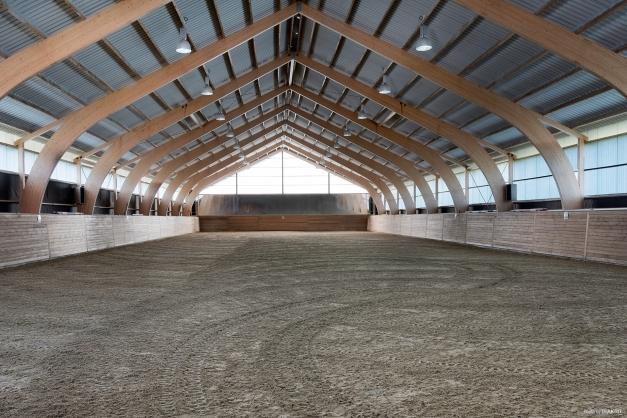 Ett mycket påkostat och fullstort ridhus med vackra limträbalkar och harmonisk ridmiljö. Mått: 66 x 22 meter (varav ridhall 22 x ca 62 meter) med lutande sarg.