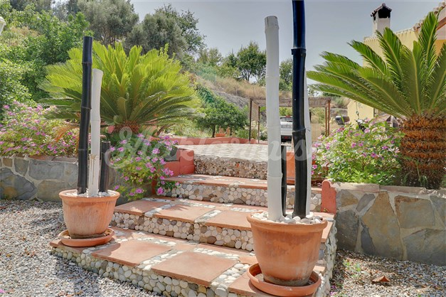 Många konstnärliga detaljer runtom i trädgården som även består av olika sorters palmer och blommande buskar och träd.