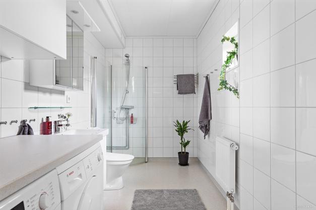 Stort och fräscht badrum. Här finns en väl tilltagen duschhörna med svängbara glasdörrar.  Separat tvättavdelning med tvättmaskin, torktumlare, bra arbetsbänk och överskåp för förvaring.