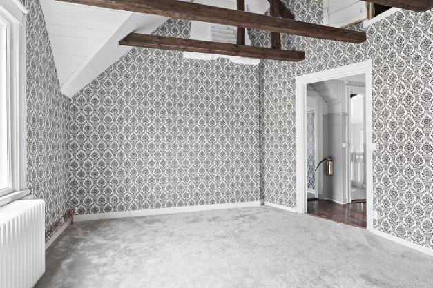 Master bedroom med ryggåstak och synliga takbjälkar