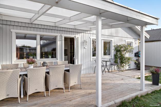 Mysig altan under tak med plats för utemöbler. Här kan man njuta från morgonkaffet till sena grillkvällar.