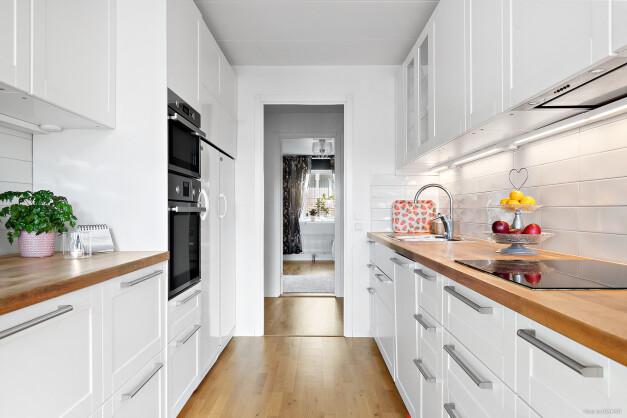 Kök med klassiskt vitt kakel och vita luckor som snyggt bryts av med bänkskiva i trä. Köket är utrustat med spis, ugn, micro, kyl, frys och diskmaskin.