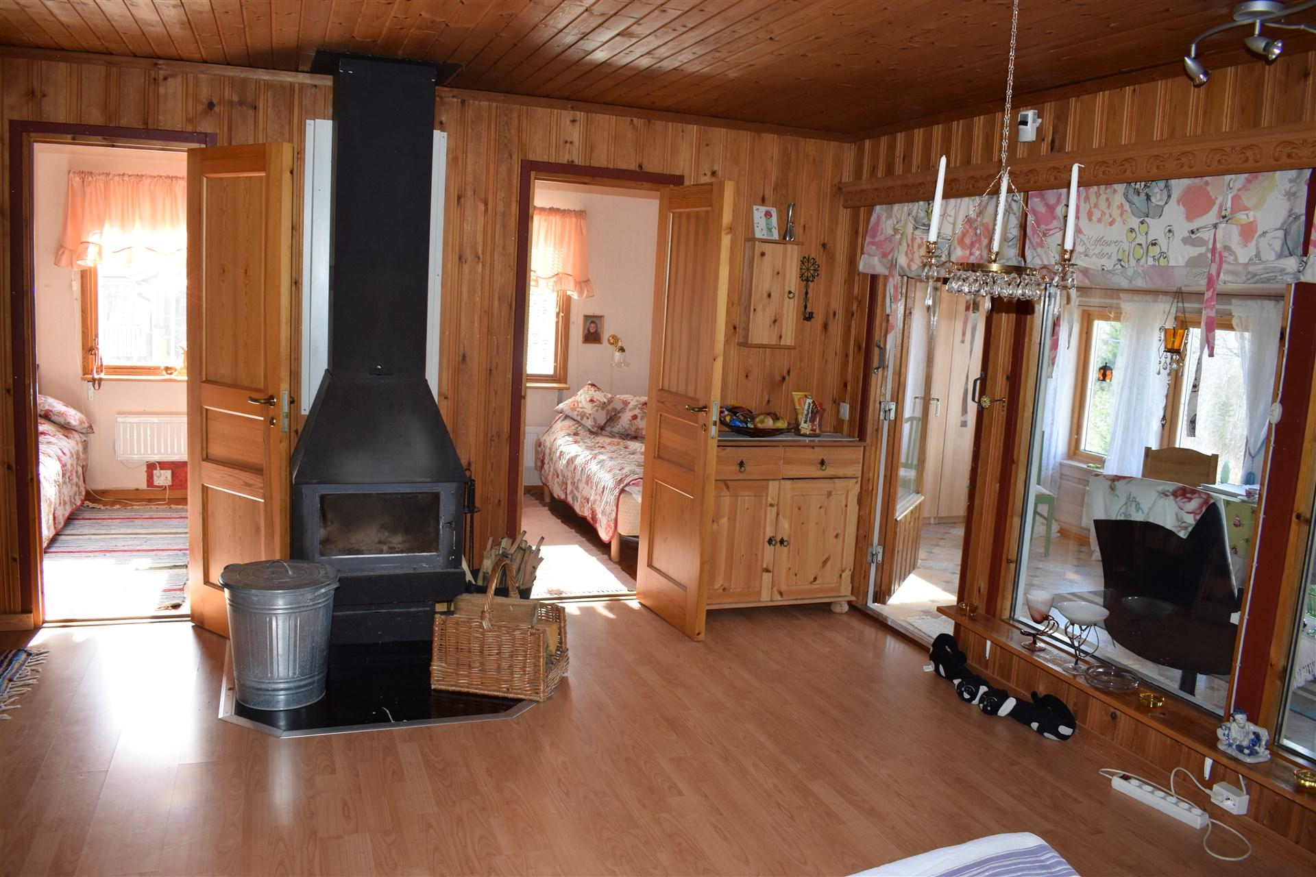 Storstuga med braskamin, mot sovrum och veranda