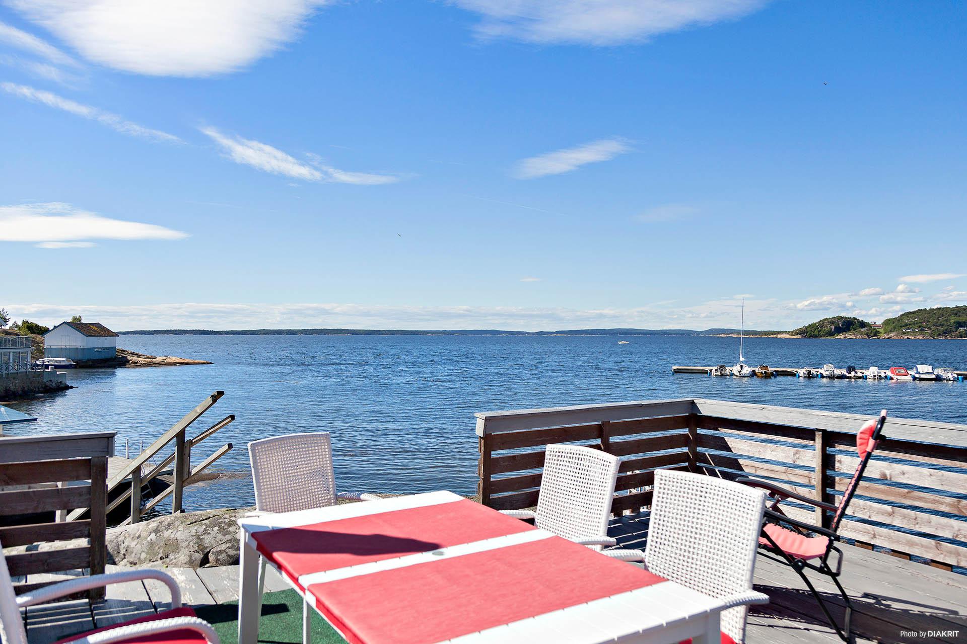 Uteplats intill havet. Solen går ned mitt i horisonten och gör platsen till en perfekt middagsplats.