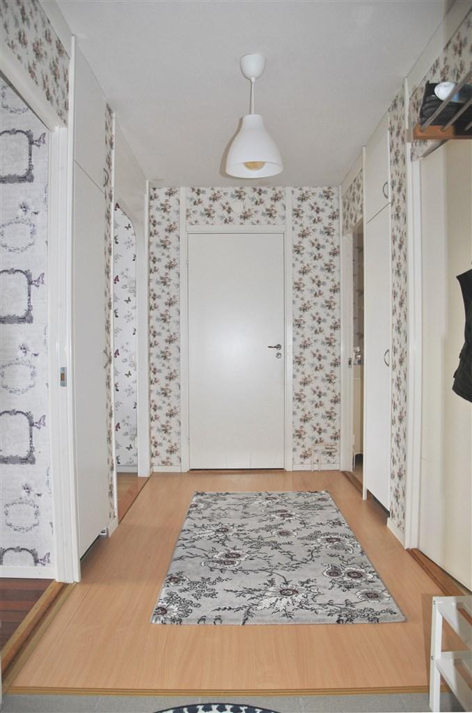 Ljus och välkomnande hall med hatthylla och platsbyggd garderob med överskåp