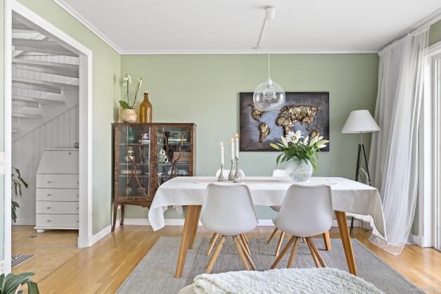 Öppet och trevligt vardagsrum med en naturlig matplats där man gärna umgås i gott sällskap.
