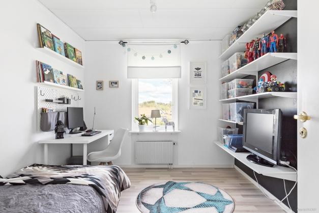 Ljust renoverat sovrum där både säng och skrivbord ryms.