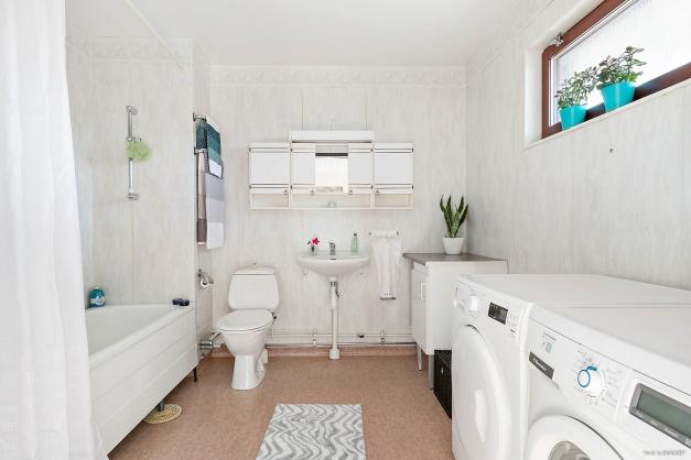Badrum med badkar, tvättmaskin och torktumlare