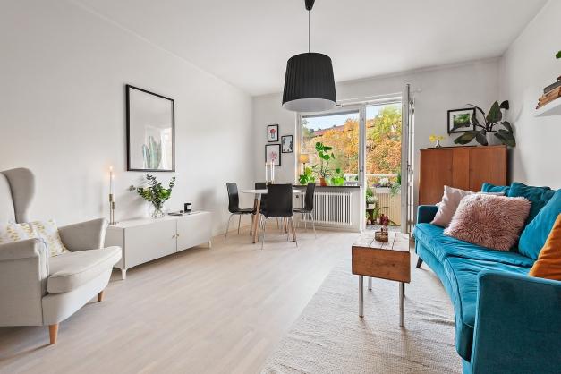 Luftigt vardagsrum med plats för soffgrupp samt matbord