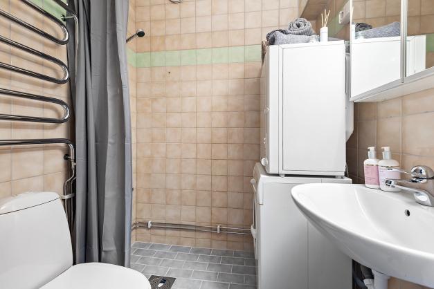 Helkaklat badrum med tvättmaskin samt torktumlare