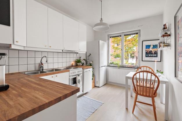 Fullt utrustat kök med vita köksluckor och ekbänkskiva