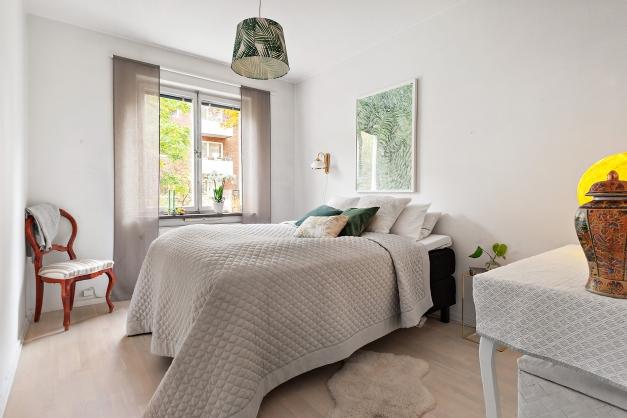 Sovrum med plats för dubbelsäng samt nattduksbord