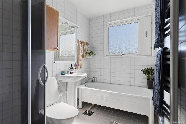 Helkaklat badrum på övre plan med både dusch och badkar.