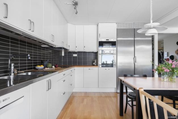Köket utrustat med kyl och frys i fullhöjd samt ugn, mikro, induktionshäll och diskmaskin.