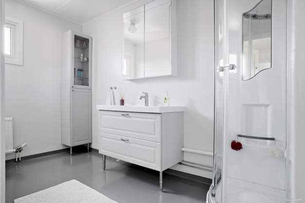 Renoverat badrum på övre plan med duschkabin.