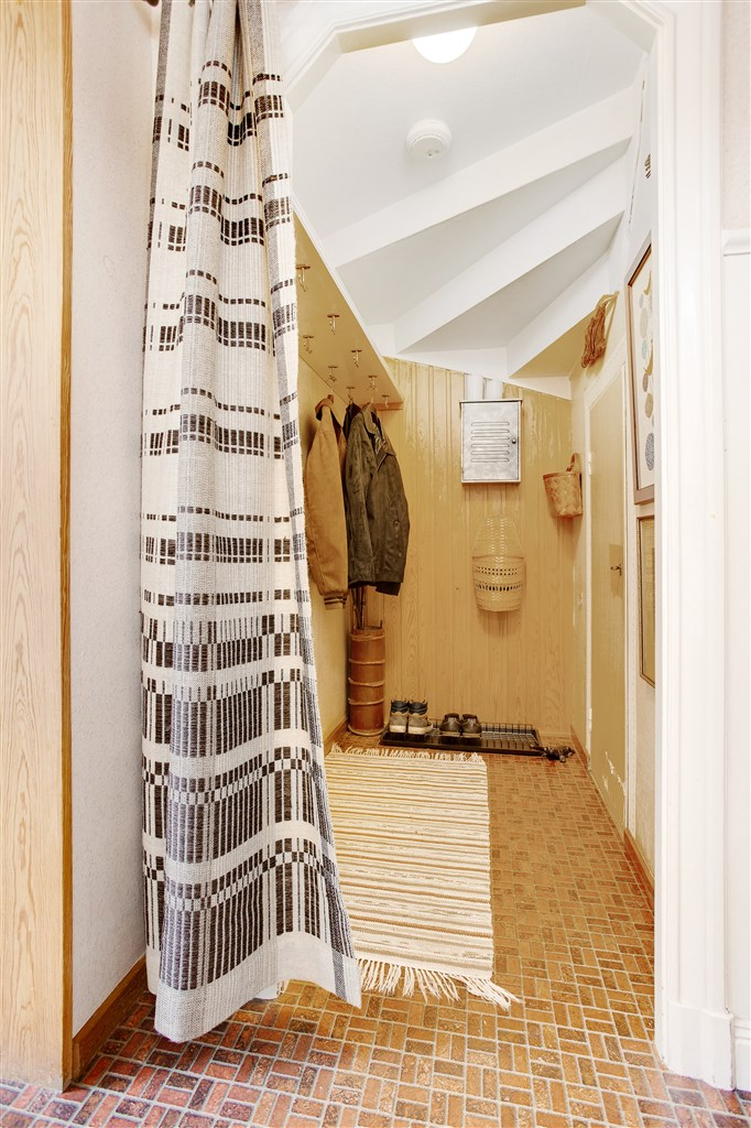 I hallen finns även ett kapprum beläget under trappen och här finns dörr ner till källarvåningen.