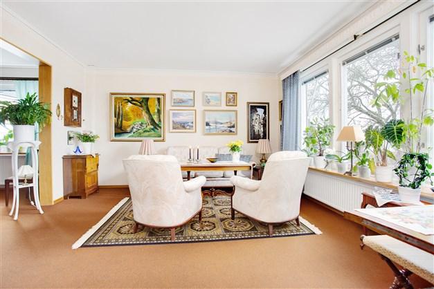 Ljust och öppet vardagsrum med portal mot matrum.