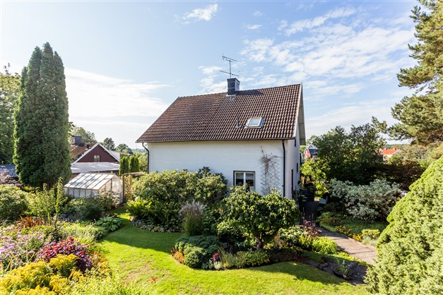 Huset omringas av en vacker trädgård med både buskar, träd och mängder av blommor. Här finns också ett växthus.