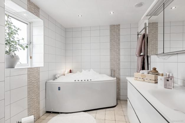 Helkaklad badrum med spabad och dusch