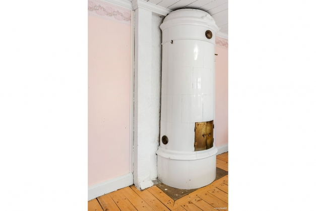 Flygeln: Lilla bostadshuset Rund kakelugn i sovrummet