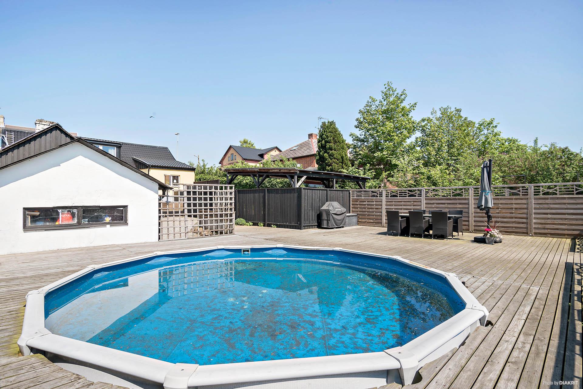 Trädäck med nedsänkt pool och uteplats mot entrén