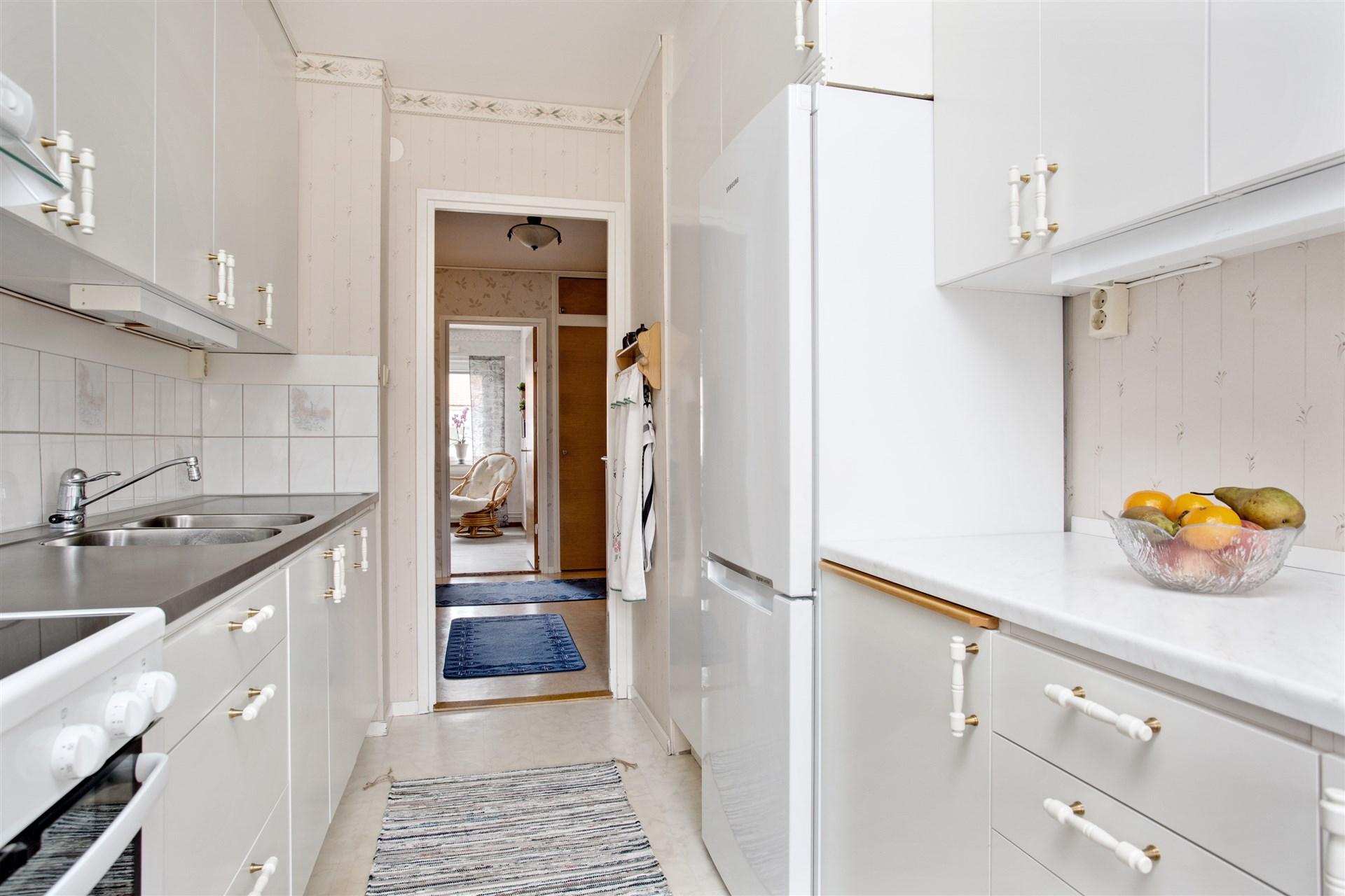 Köket med vita köksluckor och vit bänkskiva. Här finns plats för diskmaskin för den som önskar.