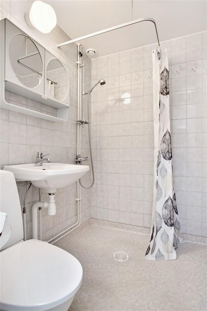 Fräsch dusch/wc med kakel på vägg och plastmatta på golv. Här finns också en handdukstork och plats för tvättmaskin.