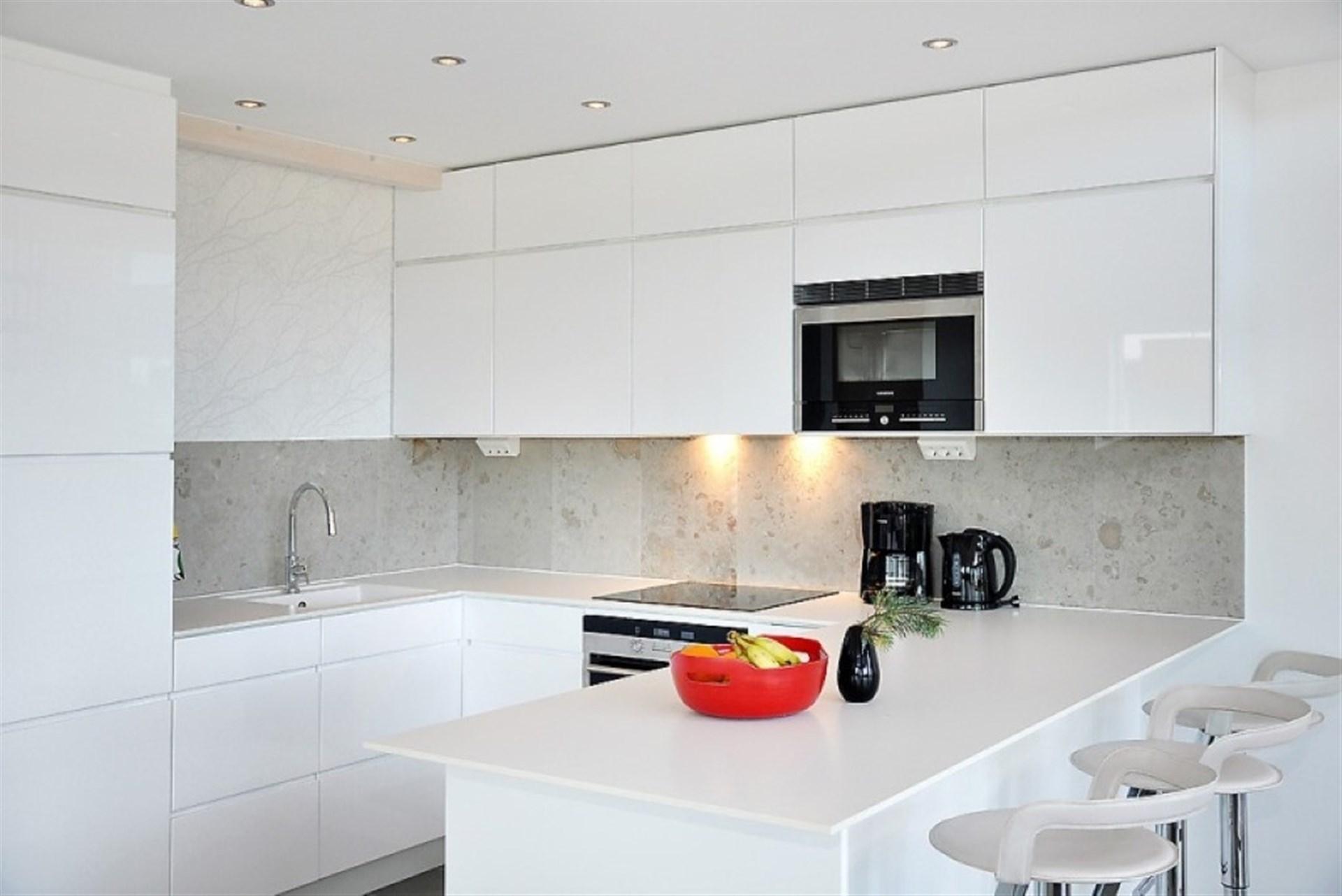 Kök i smakfull interiör med stänkskydd i kalksten