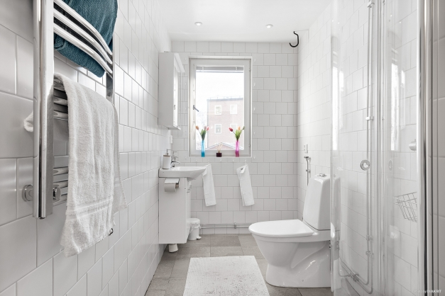 Renoverat badrum med klinkergolv och kaklade väggar i vitt