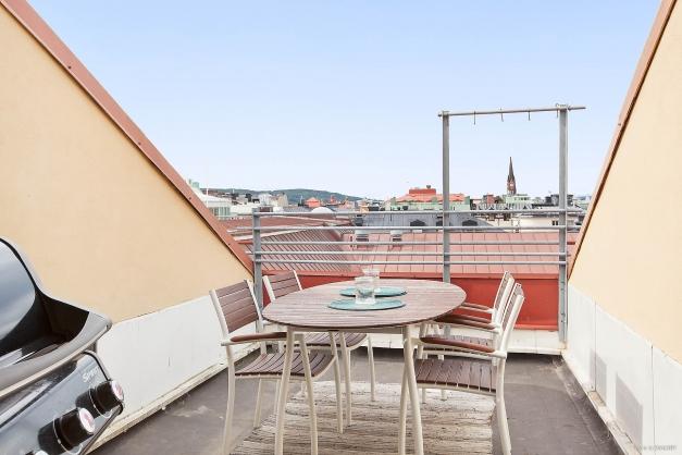 Gemensam balkong med utemöbler och grill