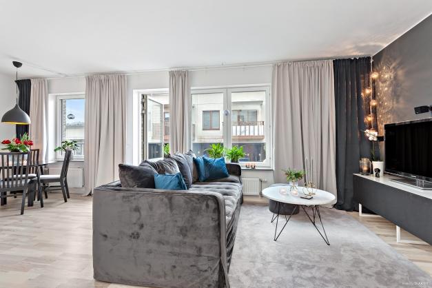 Vardagsrum med plats för stor soffa, TV samt mediamöbler
