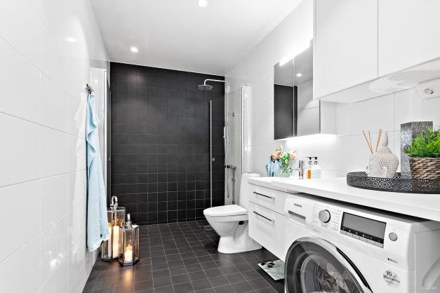 Snyggt och fräscht badrum med duschhörna och dörrpar i klarglas