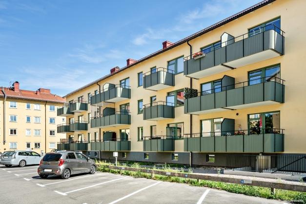 Baksidan med parkeringsplatser och de nya balkongerna i tidstypisk stil.
